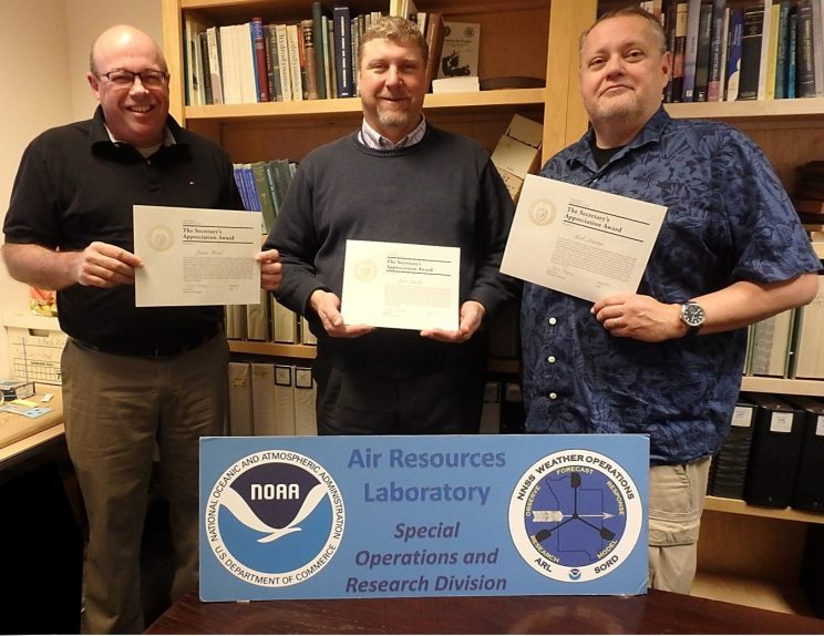 James S. Wood, Walter W. Schalk, and Ricky G. Lantrip standing in the SORD office holding their award certificates. The three are standing in front of a large panel displaying the NOAA and SORD logos.
