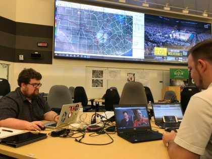 Two onsite forecasters talking with colleagues online