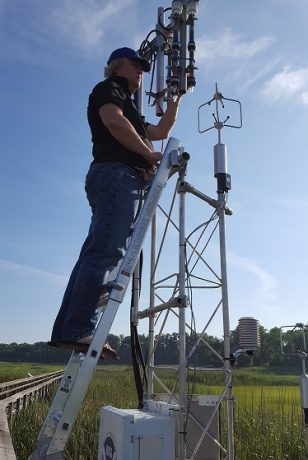 Man on a ladder installing equipment on a metal tower