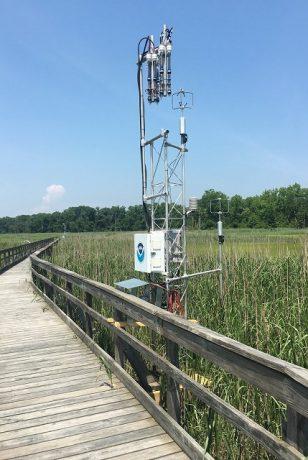 Micrometeorology tower in coastal marsh beside a pier