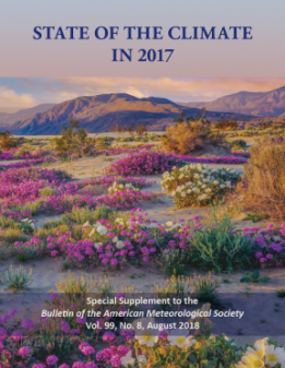 Front cover of the 2017 State of the Climate report. Flowers in the foreground and mountains in the background.