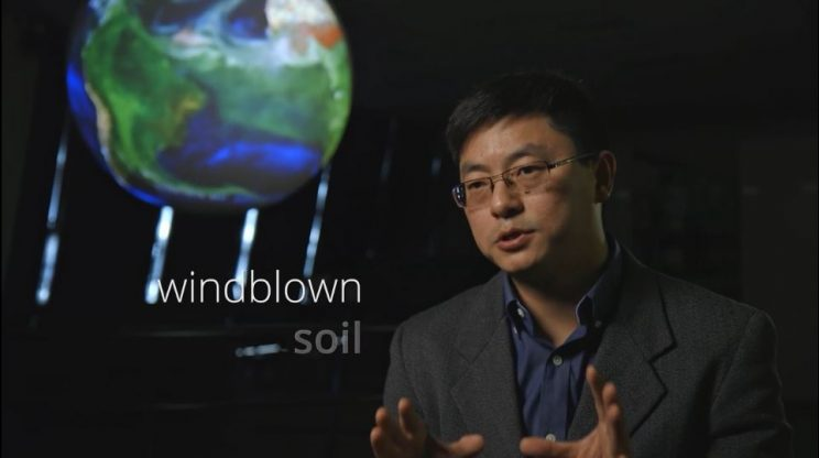 """Dr. Tong with NOAA's Science on a Sphere behind him showing a video of windblown dust and the words """"windblown soil"""" on the screen"""