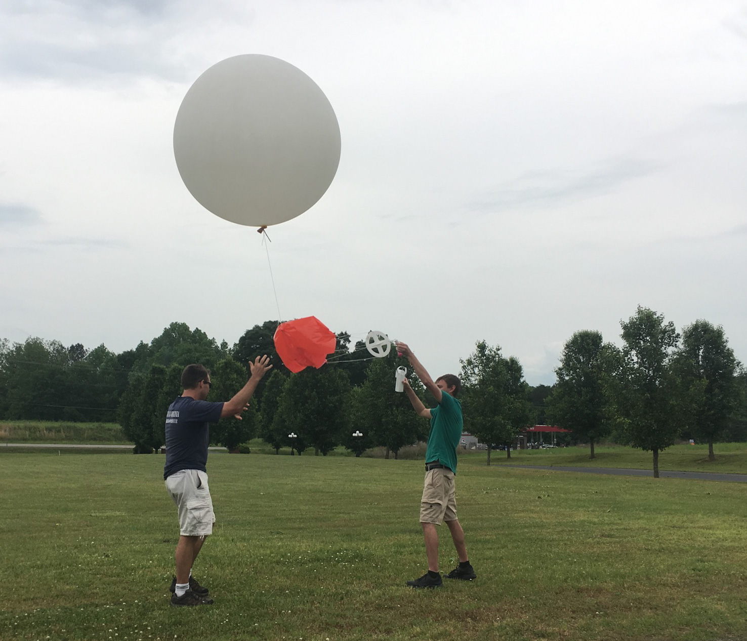 One man holding the bottom of the string as the other releases the large weather balloon