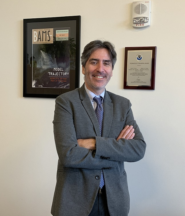 Dr. Stein standing in his office in front of a NOAA plaque and enlarged copy of an article that he authored