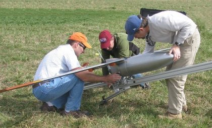 Three people attaching the sUAS to its catapult.