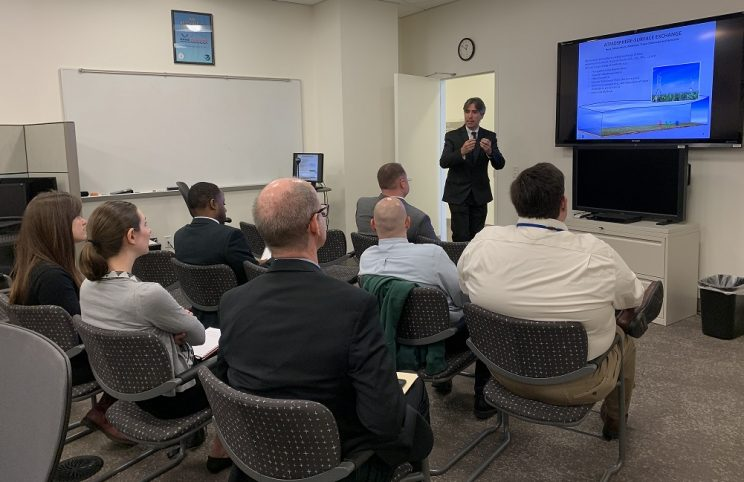 Dr. Stein presenting ARL 101 to a group of seven people