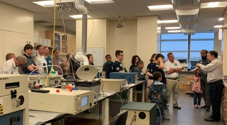 Scout troop, chaperones, and younger kids in the lab listening to Dr. Cohen