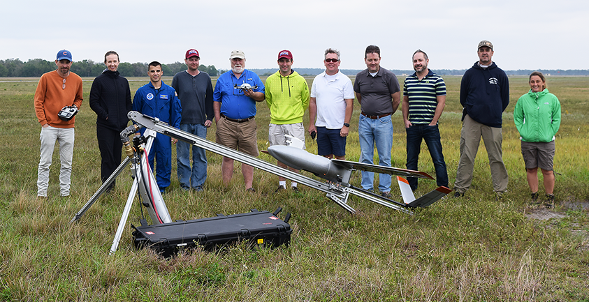 11 people standing in a field. Far left person holding a controller box, fifth from left holding an sUAS in one hand. Fixed-wing drone on a catapult with power case in front of the group.