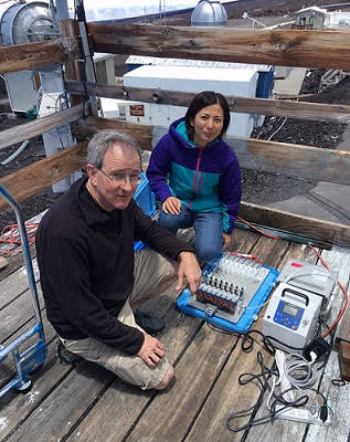 Two people kneeling on an elevated wooden deck attaching cabling to two instrument boxes.