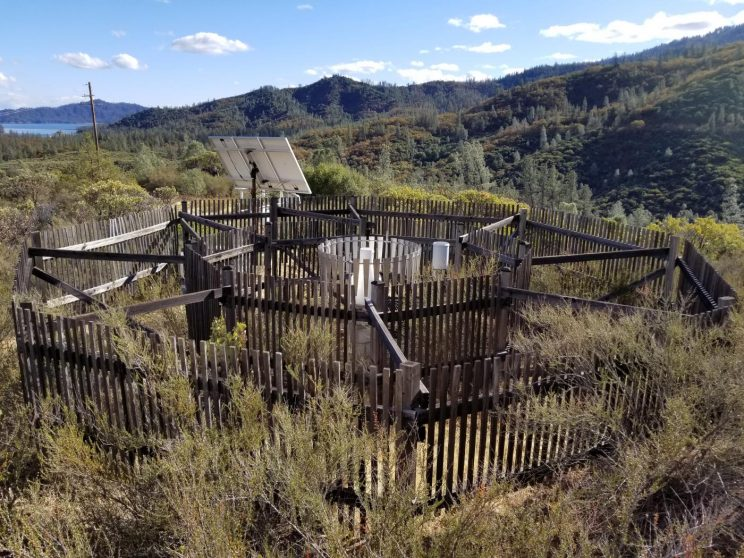 Wood fencing obscures an instrument on top of a mountain