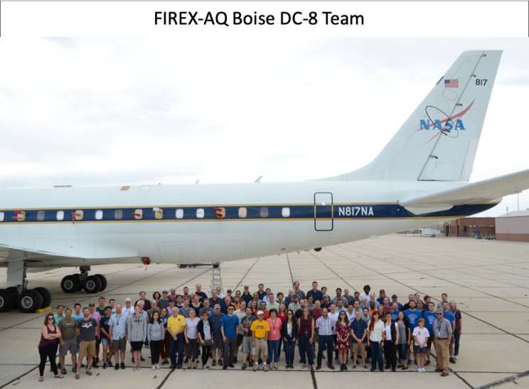 Large group of people standing under a plane with the NASA logo on the tail.