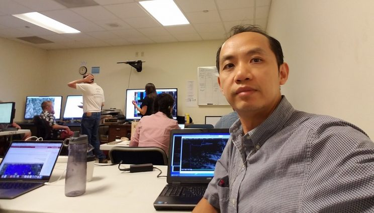 Close-up of Dr. Tang at his laptop sitting in a conference room.