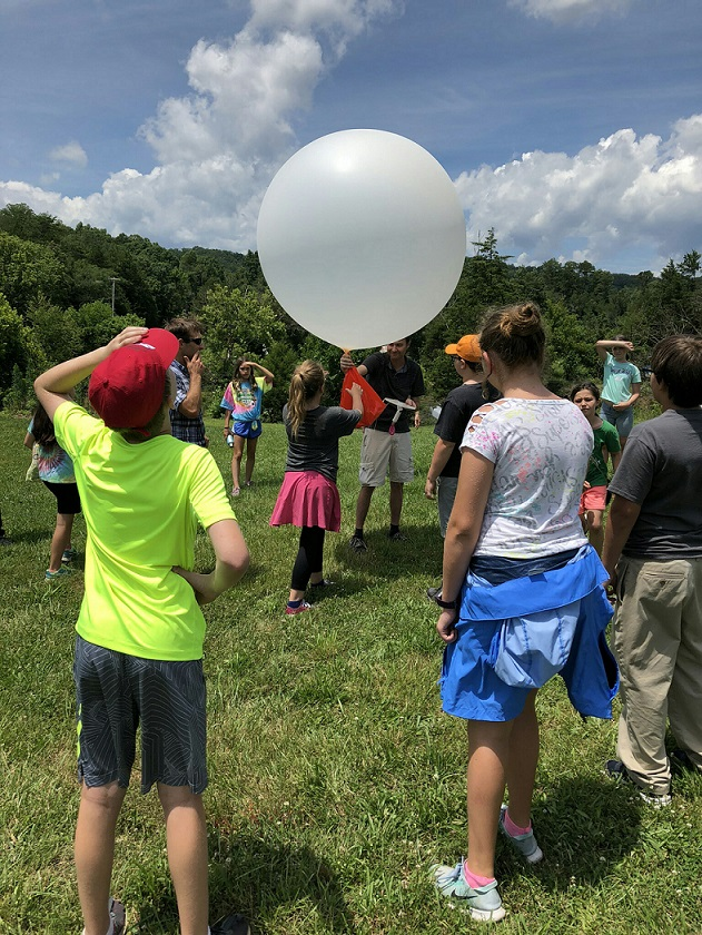 Kids in a field gathered around a man about to release a weather balloon