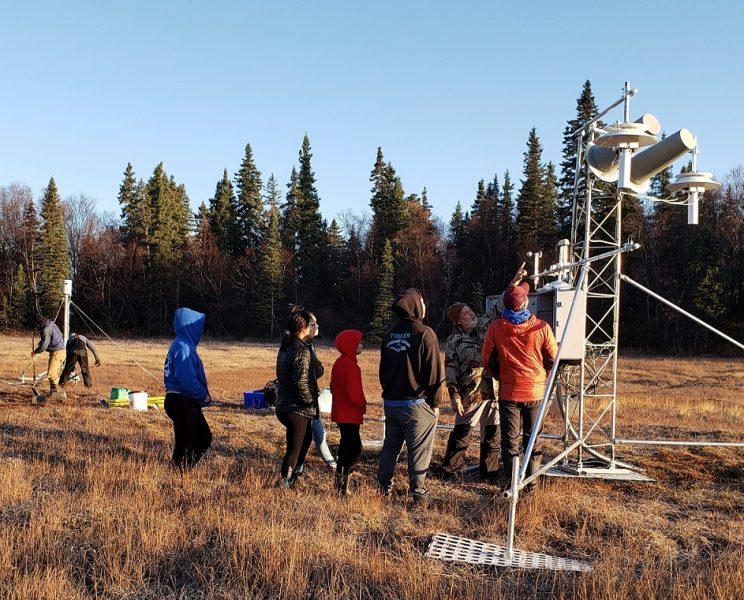 Two men with shovels in background at left. Seven people beside metal tower, one gesturing to/explaining meteorological instruments on the tower.