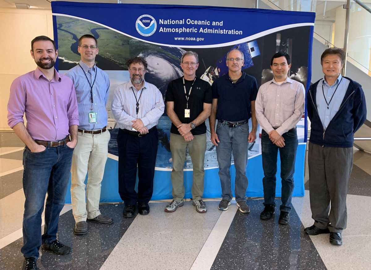 The seven recipients standing in a semi-circle in front of a display with the NOAA logo and program photos.