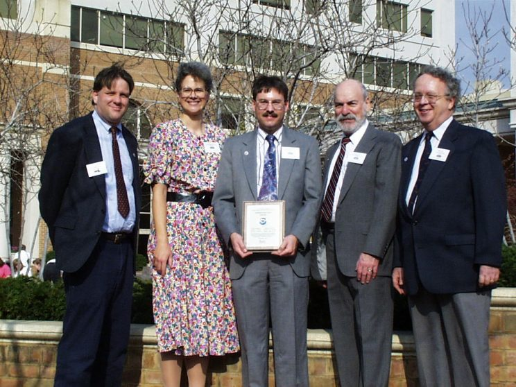 Five people (four men, one woman) in front of a tree and building. Rolph is in the middle holding a plaque with the NOAA logo.