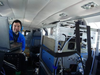View from the cockpit looking back into the plane. On the left, a man with a headset on is behind two open laptops on top of a metal shelving unit containing what looks like metal boxes with tubes and cables. On the right, the back of a metal rack containing similar, but larger metal instrument boxes is strapped around the sides and top to anchor it in place.