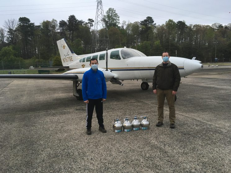 Two men wearing medical masks stand in front of a small aircraft. Four small metal cylinders are on the ground between them.