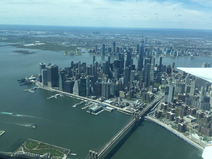 View out the window of the small aircraft, with part of the wing visible at right. Plane is above the Brooklyn Bridge and the buildings of Southern Manhattan are visible, surrounded on three sides by calm water.