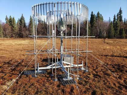 A metal grid structure surrounds a thin metal post, on top of which sits what looks like a metal bucket with a tapered top. Long, thin strips of metal hang in two circles, one inside the other, at the top of the structure, which is tethered to the ground by metal cables.